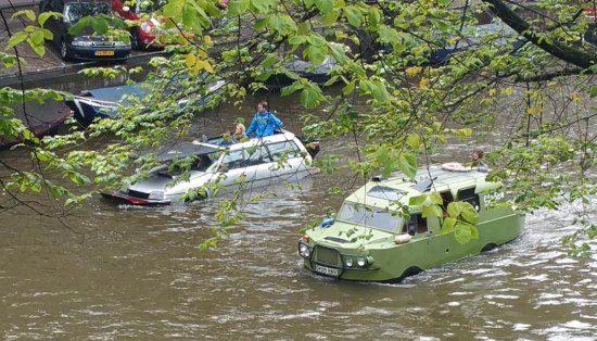 Gespot: flinke stoet amphicars in de Amsterdamse grachten